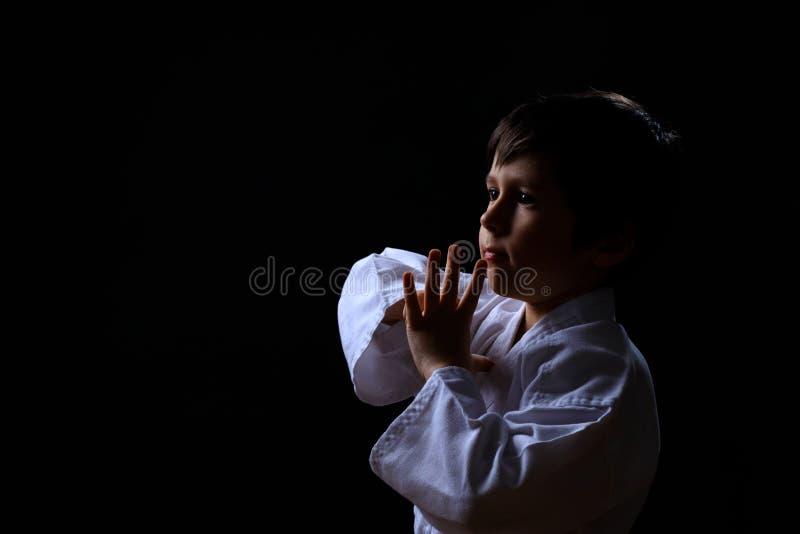 Vrai garçon de karaté dans le kimono blanc d'isolement sur le fond foncé L'enfant prêt pour des arts martiaux combattent Enfant c images libres de droits