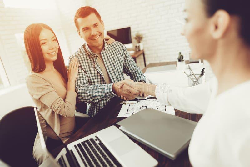 Vraie agence immobilière Jeunes couples Vente de Chambre Plans de salles Planification de bâtiment Fin d'une affaire Famille heur image libre de droits