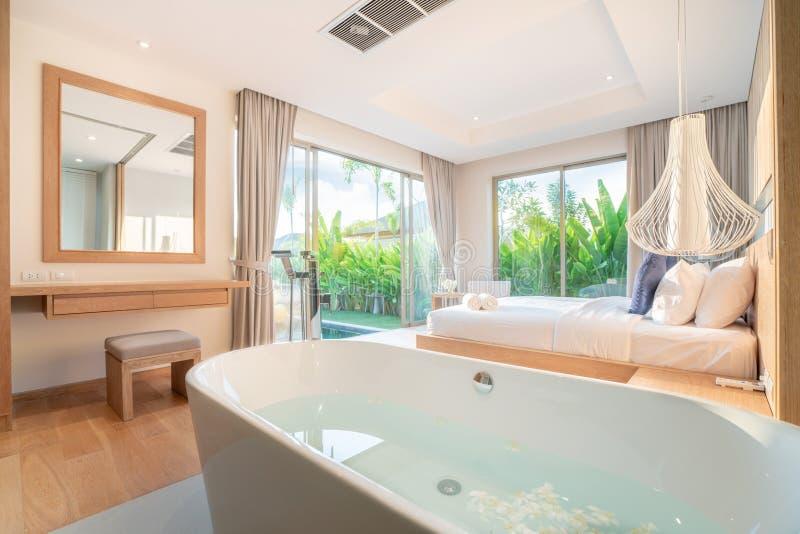 Vraie conception int?rieure de luxe dans la chambre ? coucher de la villa de piscine avec le lit confortable de roi avec la maiso photo libre de droits