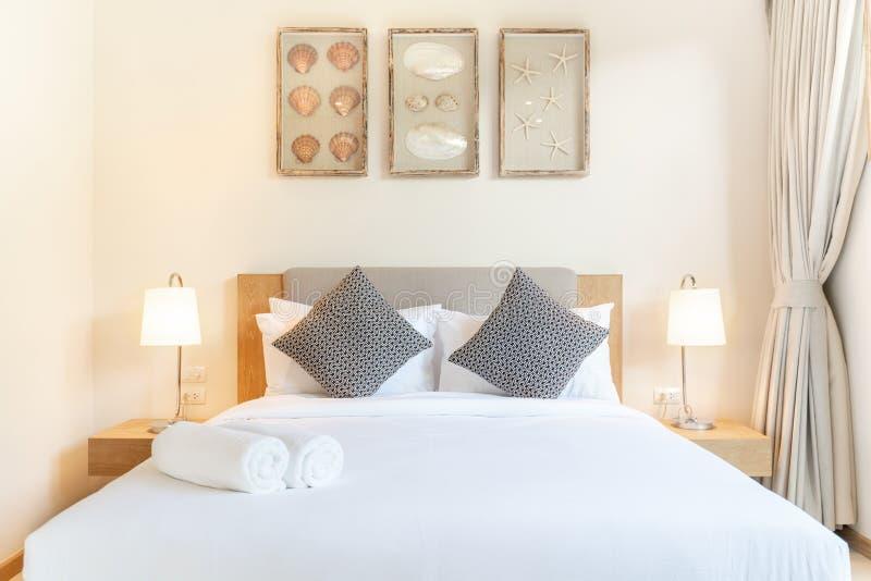 Vraie conception int?rieure de luxe dans la chambre ? coucher de la villa de piscine avec le lit confortable de roi avec la maiso photographie stock libre de droits
