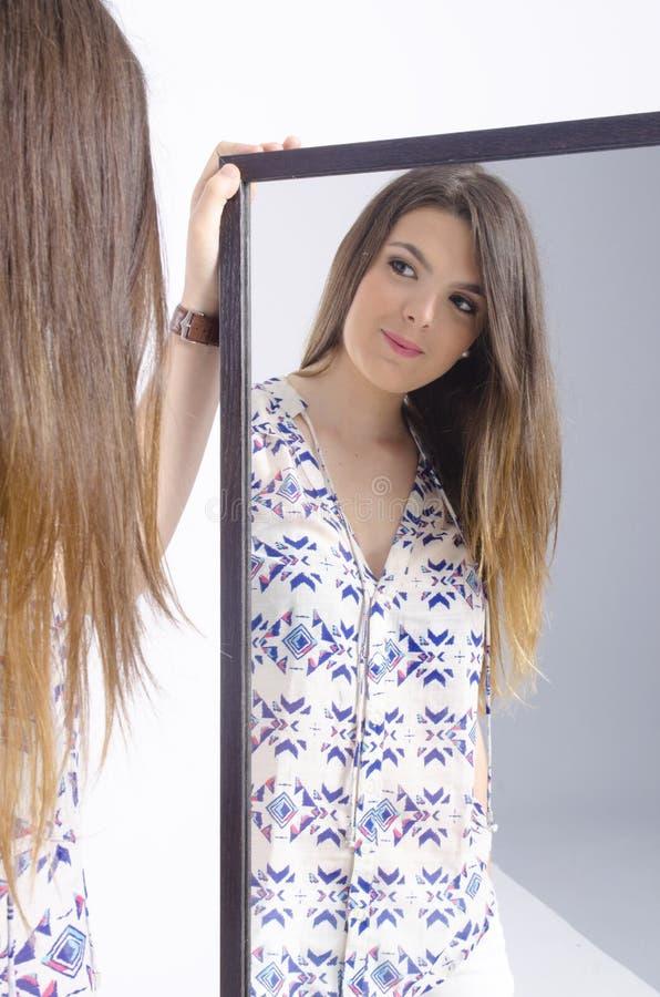 Vraie jeune femme regardant dans un miroir images stock