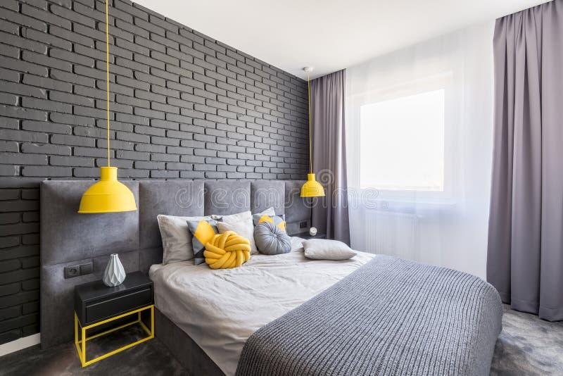 Vraie photo d'intérieur gris et jaune de chambre à coucher avec la fenêtre avec photo libre de droits