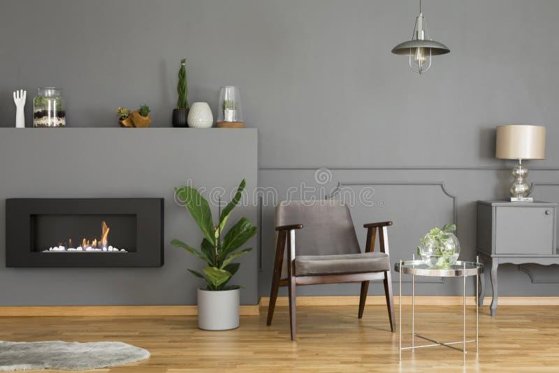 Vraie photo d'un fauteuil gris se tenant dans un livin moderne et simple images stock