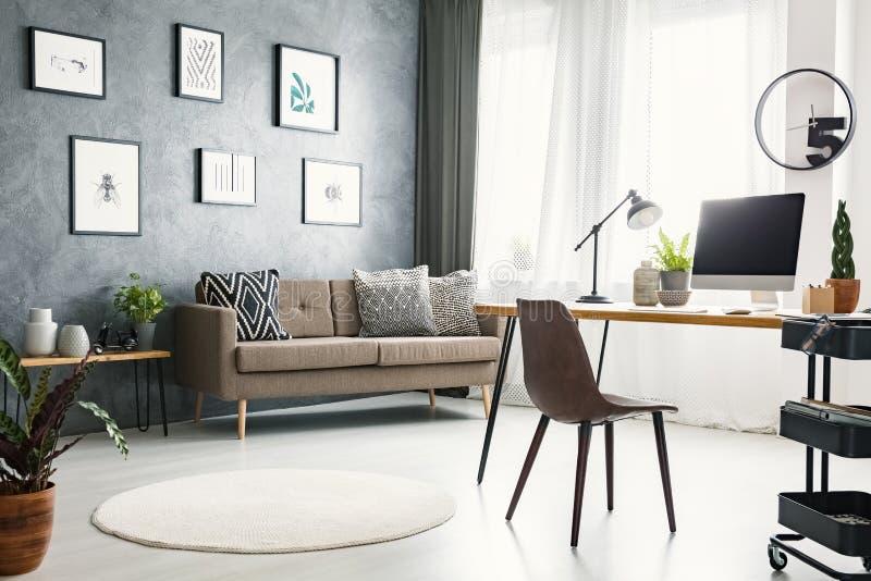Vraie photo d'un intérieur lumineux de siège social avec un sofa, graphique photos libres de droits