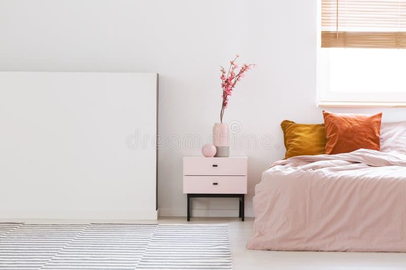 Vraie photo d'un rose, intérieur féminin de chambre à coucher avec le cush orange image libre de droits