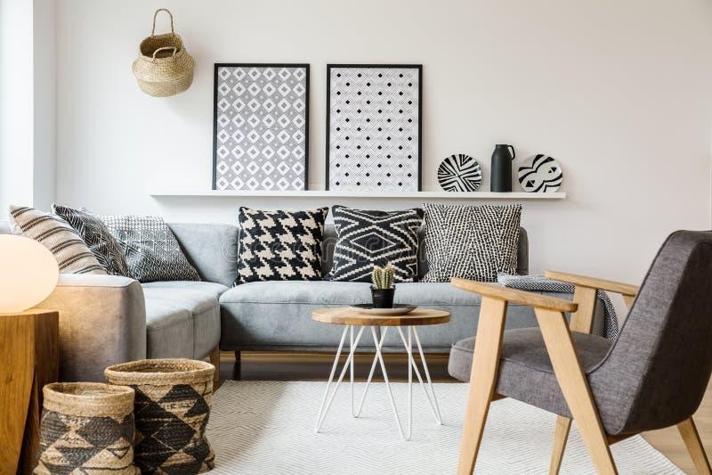 Vraie photo d'une petite table se tenant entre un sofa avec des oreillers images libres de droits