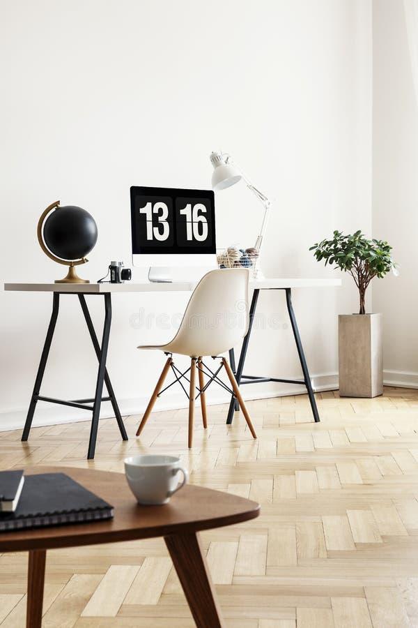Vraie photo d'une table basse avec les carnets et la tasse avec un bureau, un globe, un ordinateur et une chaise à l'arrière-plan photographie stock libre de droits