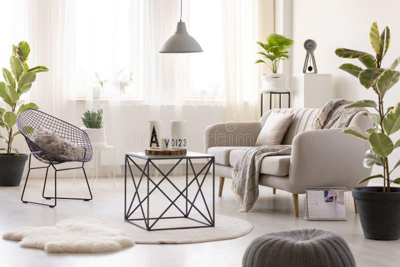 Vraie photo d'une table noire se tenant à côté d'un sofa beige et photo stock