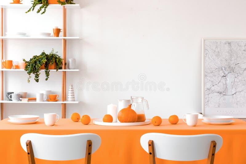 Vraie photo de deux chaises placées par la table dans la salle à manger blanche image libre de droits