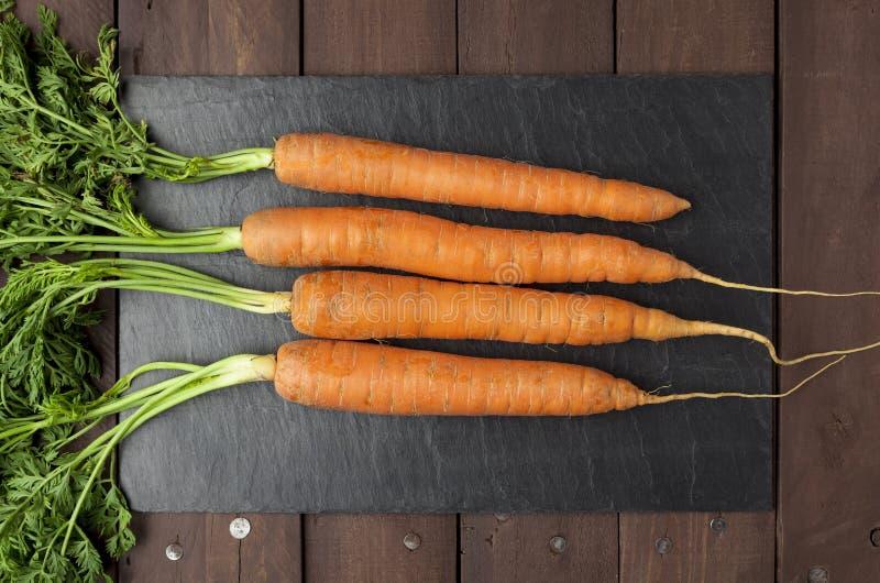 Vraies carottes de plat d'ardoise images libres de droits