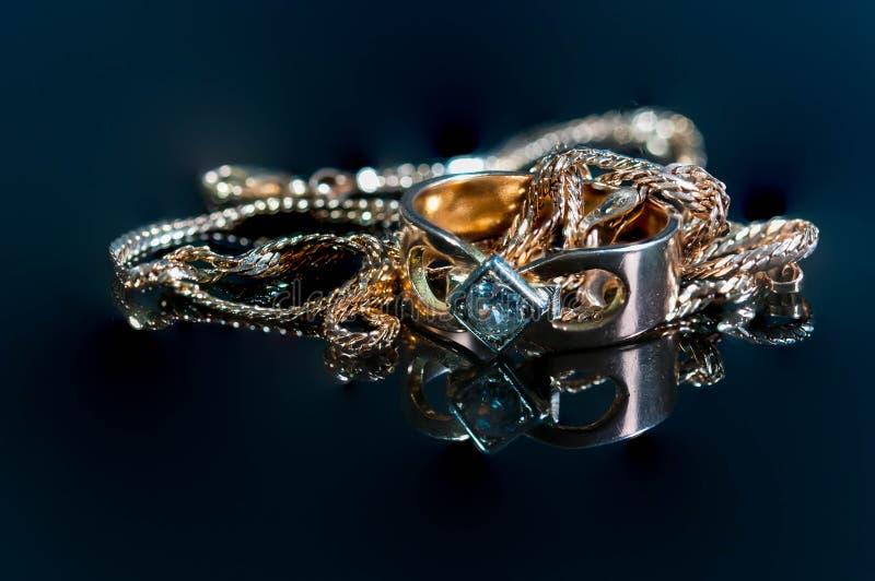 Vrais bijoux rougeoyants d'or avec de vrais diamants sur la surface brillante photographie stock