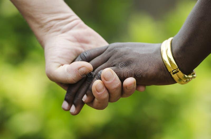 Vredessymbool - Afrikaanse en Kaukasische holdingshanden samen op vage achtergrond royalty-vrije stock fotografie