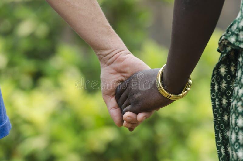 Vredessymbool - het Afrikaanse en Kaukasische vrouwen samenhouden stock foto's