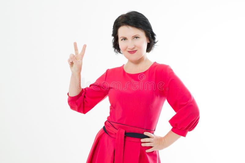 Vredesteken Mooie glimlachende middenleeftijds donkerbruine vrouw in rode die kleding op witte achtergrond wordt geïsoleerd De ru stock afbeeldingen