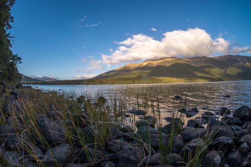 Vreedzaam landschap van een meer, een wolkenvorming, een heuvel en een blauwe hemel royalty-vrije stock fotografie