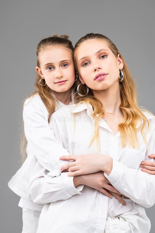 Vreedzaam meisje die strak haar aantrekkelijke oudere zuster koesteren stock afbeelding