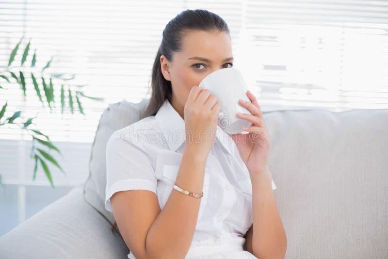 Vreedzame aantrekkelijke vrouw het drinken koffie stock afbeeldingen