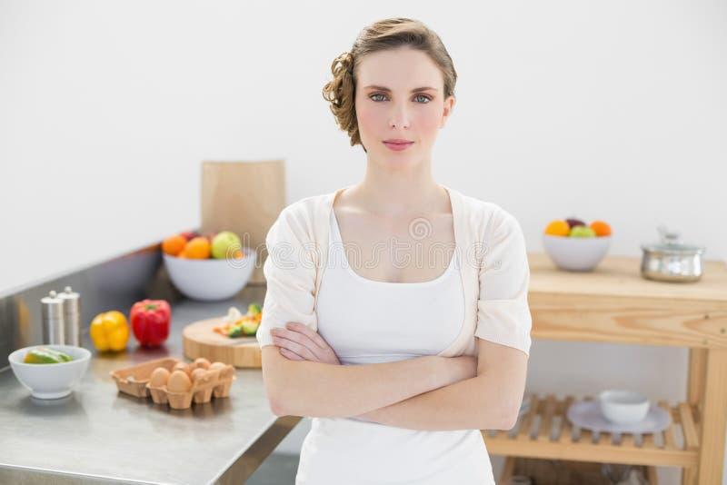 Vreedzame ernstige vrouw die zich met wapens bevinden die in keuken worden gekruist stock fotografie