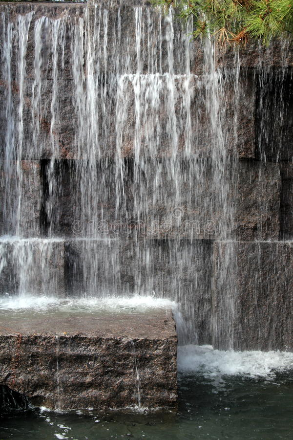 Vreedzame geluiden van waterval die over gesneden steen tuimelen stock afbeeldingen