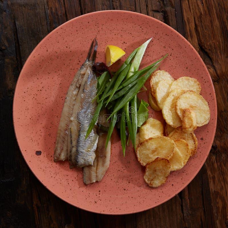Vreedzame haringen met gebraden aardappels en ui stock afbeeldingen
