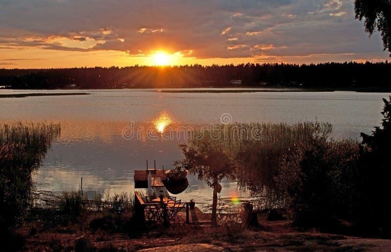 Vreedzame kleurrijke zonsondergang en boot door een meer royalty-vrije stock afbeeldingen