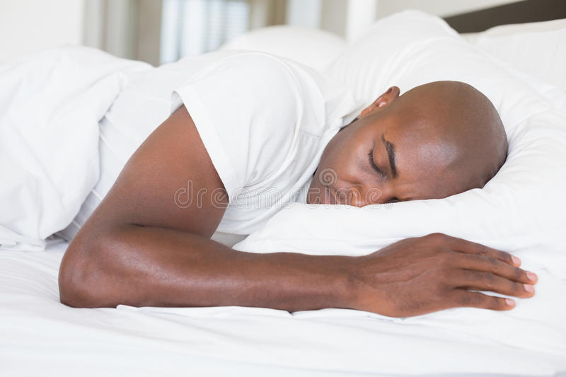 Vreedzame mensenslaap in bed stock afbeelding