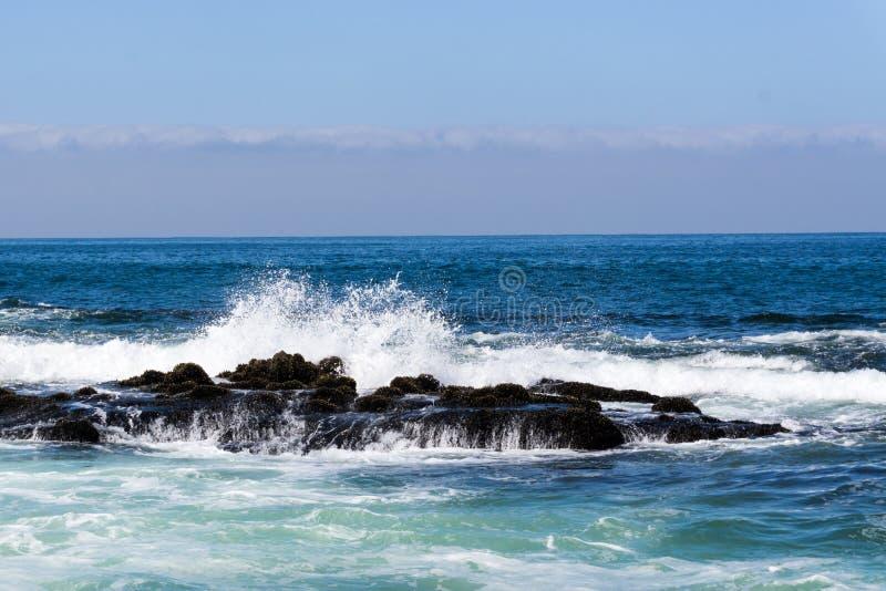 Vreedzame Oceaan met Golven die in Rotsen verpletteren royalty-vrije stock foto's