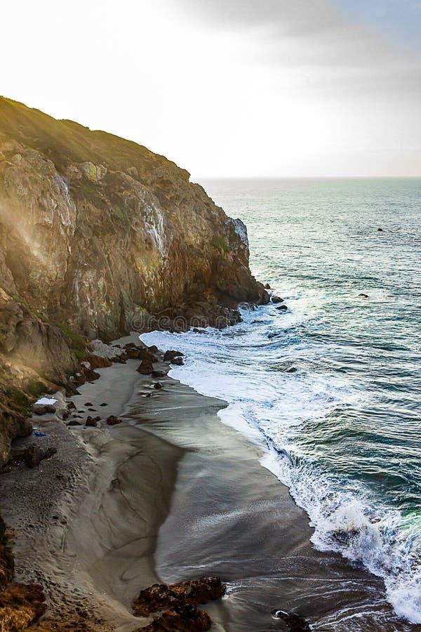 Vreedzame oceaanhorizon, met golven die op donkere zandige strandinham breken royalty-vrije stock afbeelding