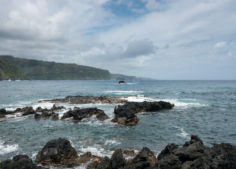 Vreedzame oceaanonderbrekingen tegen lavarotsen in Keanae royalty-vrije stock afbeelding