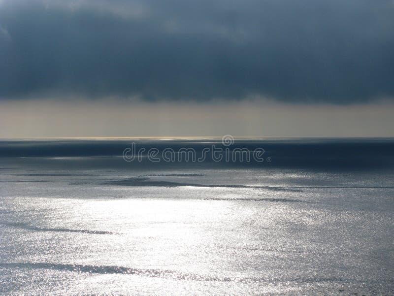 Vreedzame oceaanoverzees en cloudscape met onheilspellende wolken stock afbeelding