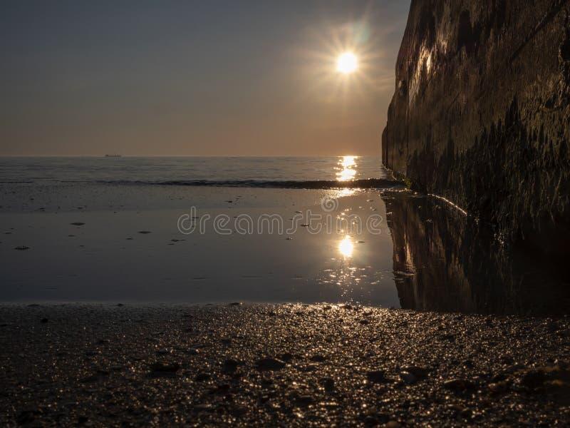 Vreedzame ochtendoverzees met de zon het toenemen en een steenpijler stock afbeeldingen
