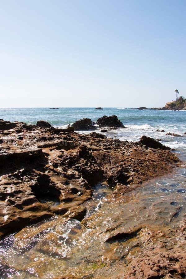 Vreedzame rotsachtige kustlijn die brandingsgebied tonen royalty-vrije stock afbeelding