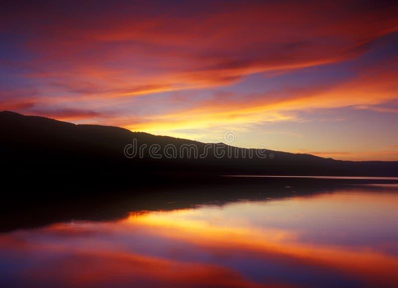 Vreedzame zonsondergang op een kalm meer stock foto