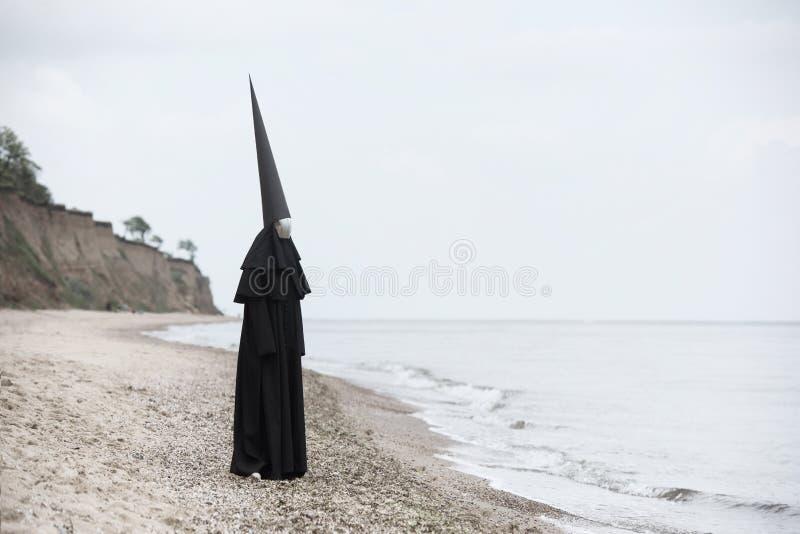 Vreemd cijfer in zwarte mantel met het spiegelgezicht in kust stock afbeelding