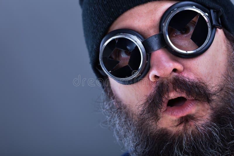 Vreemde baardmens die explosieve situatie of aanbieding bekijken - close-up stock foto