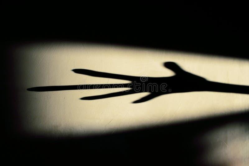 Vreemde Schaduw op de Muur Vreselijke Schaduw abstracte achtergrond Zwarte Schaduw van een Grote Hand op de Muur Silhouet van een stock foto's