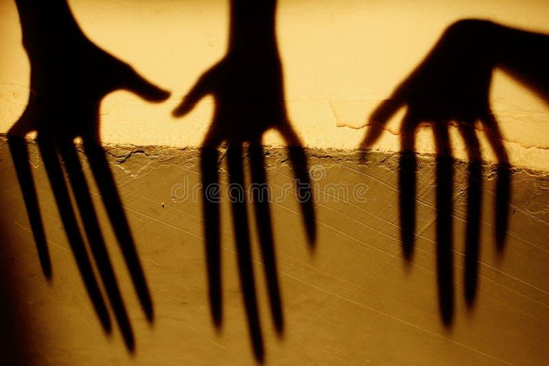 Vreemde Schaduw op de Muur Vreselijke Schaduw abstracte achtergrond Zwarte Schaduw van een Grote Hand op de Muur Silhouet van een stock foto