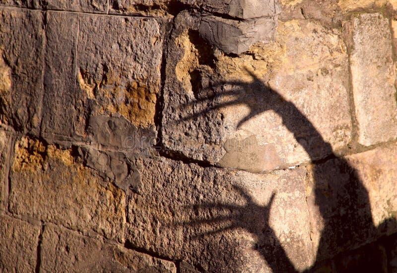Vreemde schaduw van twee handen op een oude steenmuur Zwarte schaduw, vrouwelijke hand stock foto's