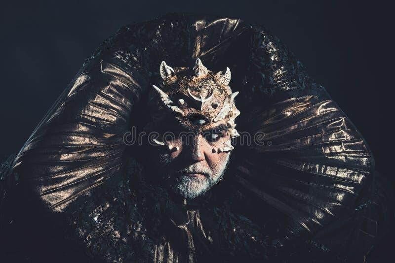 Vreemdeling, demon, tovenaarsmake-up Mens met derde oog, doornen of wratten Demon met gouden kraag op zwarte achtergrond verschri royalty-vrije stock afbeelding