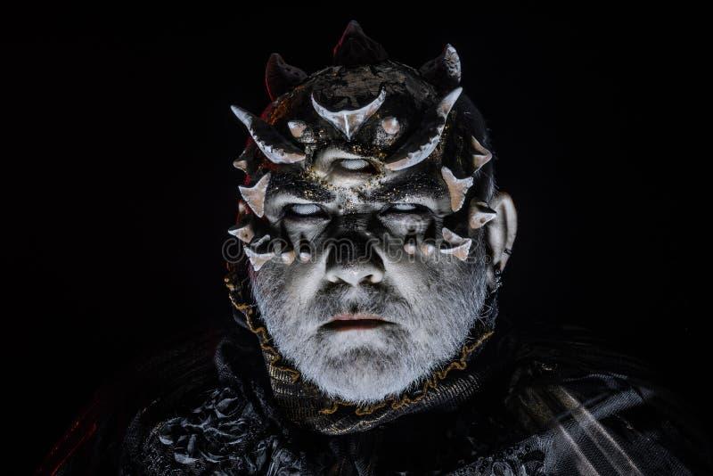 Vreemdeling, demon, tovenaarsmake-up Verschrikking en fantasieconcept Mens met derde oog, doornen of wratten Demon op zwarte royalty-vrije stock foto