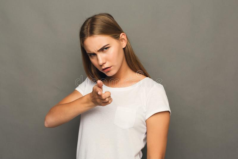 Vresig flicka som pekar fingret på kameran arkivfoton
