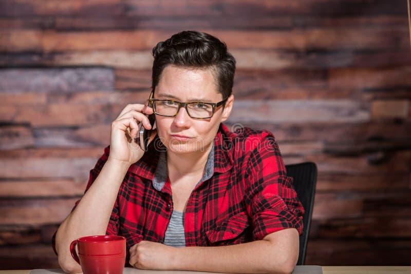 Vresig kvinna på telefonen arkivfoton