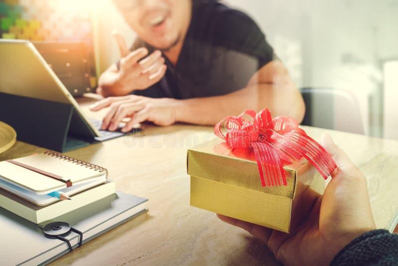 Vreugde van het Geven van Kerstmis bedrijfs creatieve ontwerperhand die zijn collega geven stock foto
