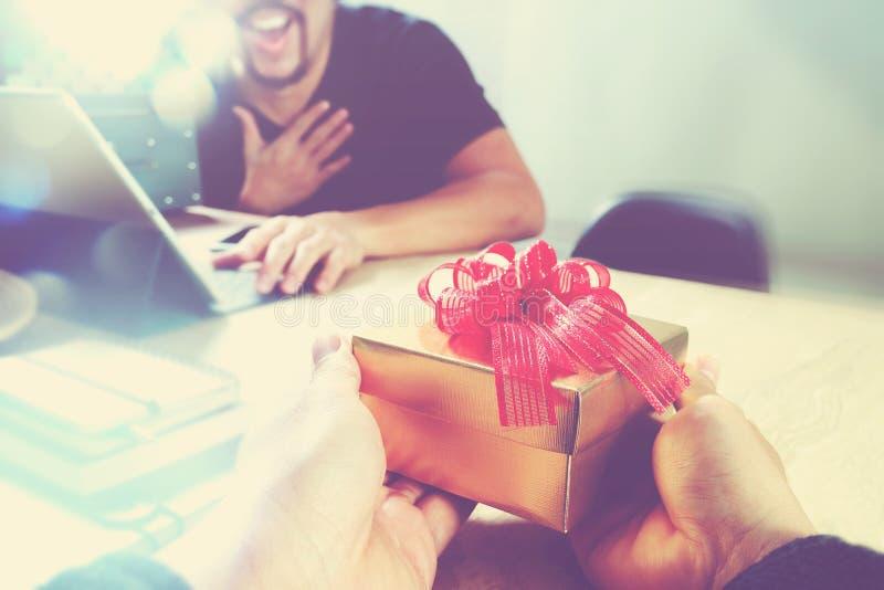 Vreugde van het Geven van Kerstmis bedrijfs creatieve ontwerperhand die zijn collega geven royalty-vrije stock foto