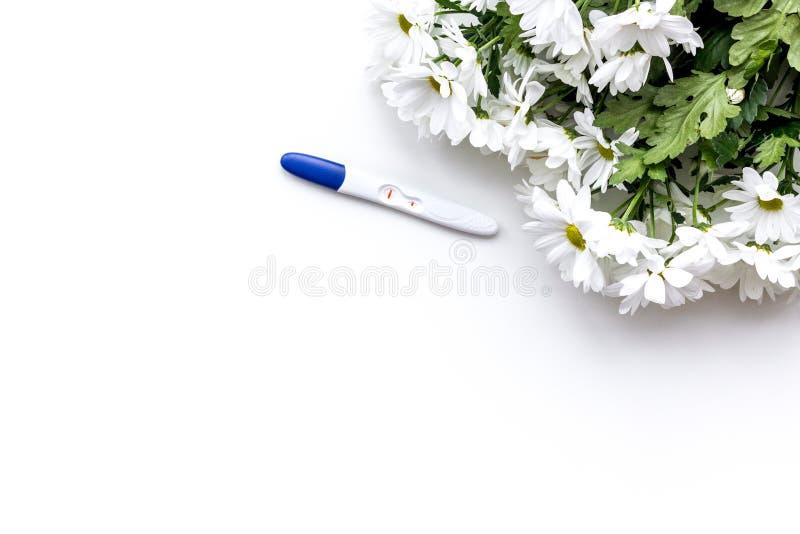 Vreugde van langverwachte zwangerschap Zwangerschapstest met twee strepen dichtbij bloemen op de witte ruimte van het achtergrond stock foto