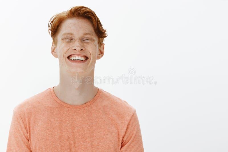 Vreugdevol en studioschot die van knappe zekere volwassen roodharigekerel met sproeten en heldere glimlach, grijnzen staren stock afbeelding