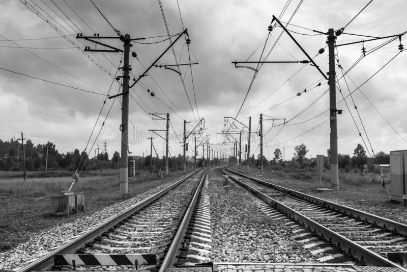 Vrida sig och lämna i avståndsjärnvägsspåren och de elektriska polerna längs dem royaltyfria foton