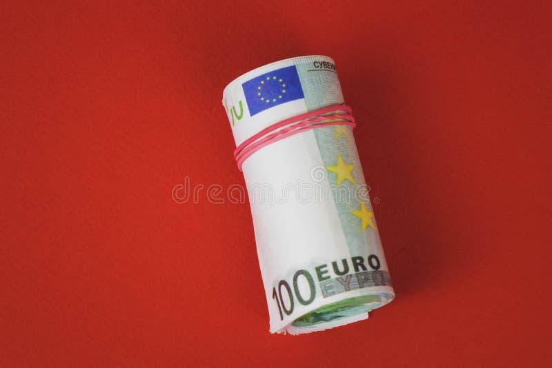 Vridet bunta 100 euroräkningar som isoleras på röd bakcground royaltyfri bild