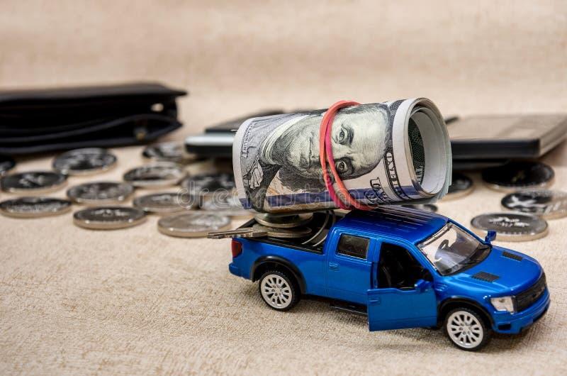 Vridna dollar på en leksakbil på bakgrunden av mynt royaltyfri foto