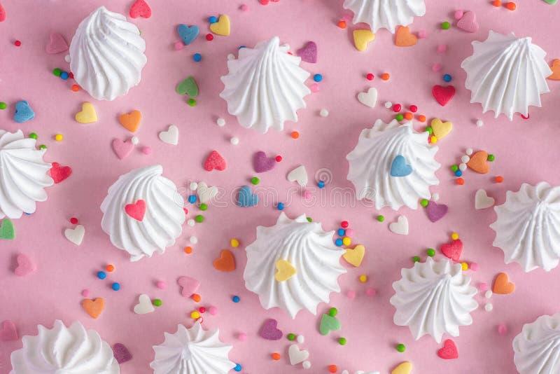 Vridna marängar med konfektaffärgarneringar på rosa backgr royaltyfria foton